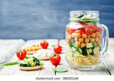 Pasta chickpeas cucumber tomatoes spinach goat cheese salad in a jar. toning. selective focus