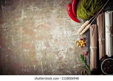 Pasta in a composition with vegetables and kitchen accessories on an old background