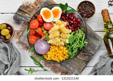 Pasta with corn, egg, tomato, arugula, in a bowl. Bowl Buddha Top view. free space for your text.