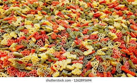 Pasta different colors background. Multicolor pasta texture pattern background. Red green yellow orange color pasta pile in supermarket for sale. Macaroni pasta big heap colorful pattern or background