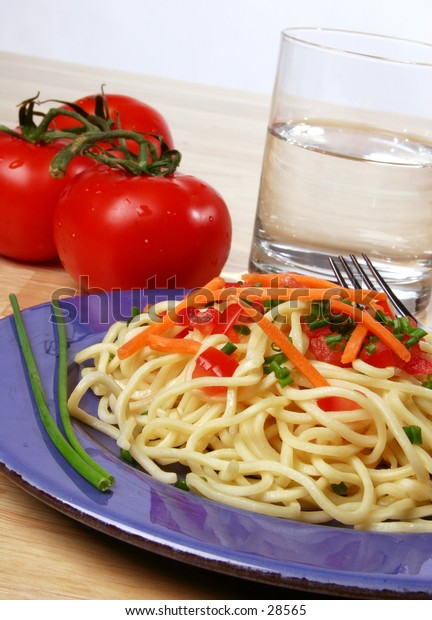 pasta dinner plate with noodles, tomato, carrots, and chives.