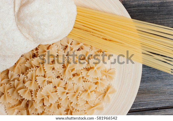 Pasta farfalle, spaghetti, cherry tomatoes, wooden paddle for frying farfalle on a tree.