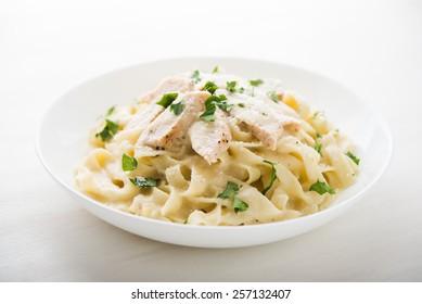 Pasta fettuccine alfredo mit Huhn, Parmesan und Petersilie auf weißem Hintergrund, Nahaufnahme. Italienische Küche.