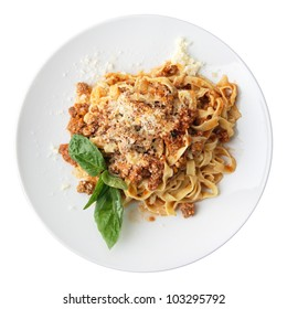 Pasta fettuccine Bolognese with leaf of basil on a white round dish isolated over white background. Top view.