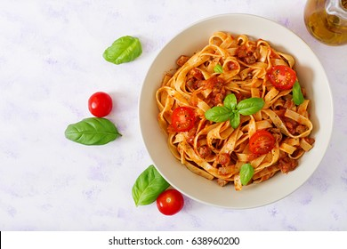 Pasta Fettuccine Bolognese with tomato sauce in white bowl. Flat lay. Top view