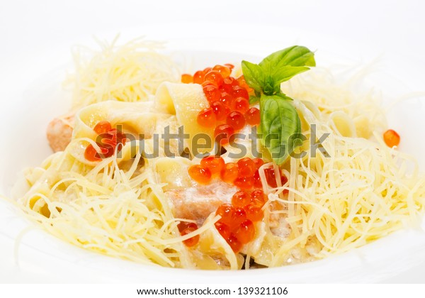 pasta with fish red caviar and cheese on the table in a restaurant