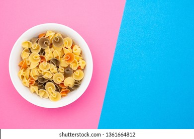 Pasta in the form of mushrooms in a white small bowl on a pink background with copy space. Top view.