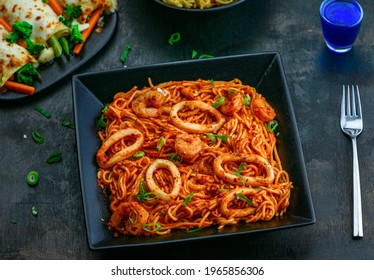 Pasta Frutti Di Mare Pasta Marinara Sauce Shrimps Calamari Spring Onion Chili Flakes in a ceramic black plate with fork and starter drink on a wooden table