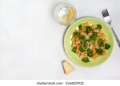 pasta fusilli with broccoli, with spinach creamy sauce on a green plate close-up