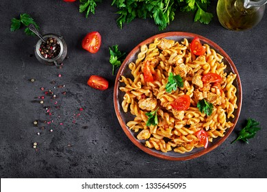 Pasta Fusilli  with tomatoes, chicken meat and parsley on plate on dark table. Top view. Flat lay