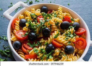 Pasta (Fusilli) in white pan on black slate background. Vegetarian, cooked with tomatoes, olives, garlic and parsley. Top view.