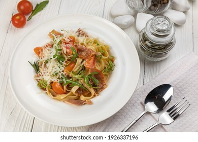 Pasta with herbs and tomatoes on a white wooden table