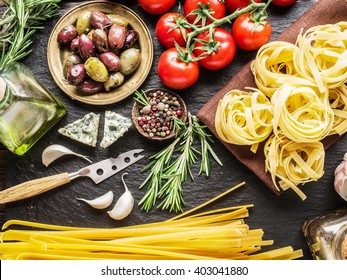 Pasta ingredients. Cherry tomatoes, spaghetti pasta, rosemary and spices on a graphite board.