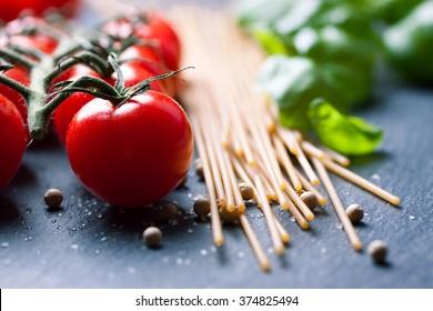 Pasta ingredients. Cherry-tomatoes, spaghetti pasta, fresh basil, spices on a dark stone background, closeup, selective focus