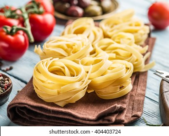 Pasta ingredients. Cherry-tomatoes, spaghetti pasta and spices on the wooden table.