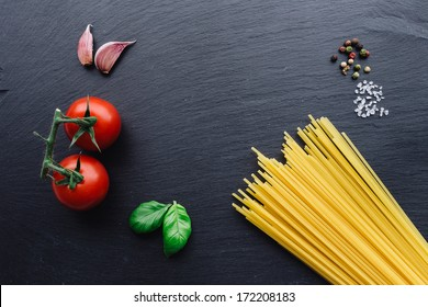 Pasta ingredients concept on black slate background viewed from the top