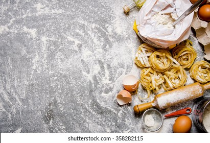 Pasta with ingredients - flour, eggs and different tools for cooking. On the stone table. Free space for text . Top view