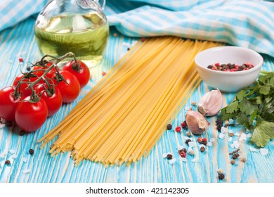 Pasta ingridients, blue checkered towel and spice on blue wooden surface.