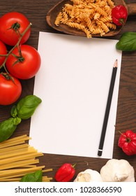 Pasta or Italian food concept background with an empty paper sheet and pencil on a wooden table