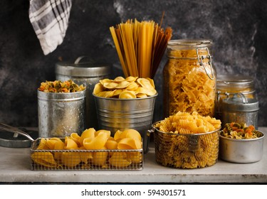 Pasta. italian pasta. Italian food cooking ingredients with tagliatelle, penne, tortellini, ravioli, mafalda pasta in storage jars. Mediterranean food.