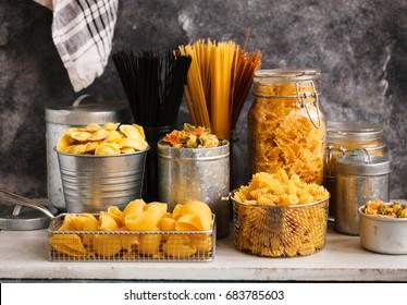 Pasta. italian pasta. Italian food cooking ingredients with tagliatelle, penne, tortellini, ravioli, mafalda pasta in storage jars.