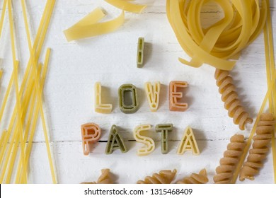 Pasta love concept with  raw alphabet pasta on white wooden background