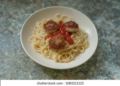Pasta and meat balls on marble table