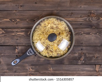 Pasta with meat in the Navy in a pan under a glass lid, top view