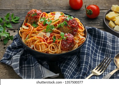 Pasta with meatballs, parmesan and tomato sauce in a clay bowl. Homemade Italian spaghetti on a rustic wooden table.