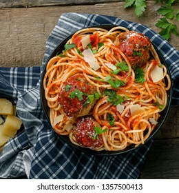 Pasta with meatballs, parmesan and tomato sauce in a clay bowl. Homemade Italian spaghetti on a rustic wooden table. Top view shot.