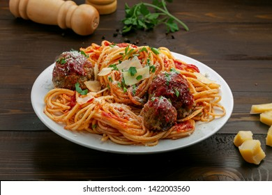 Pasta with meatballs, parmesan and tomato sauce on a plate.  Homemade Italian spaghetti on a rustic wooden table.