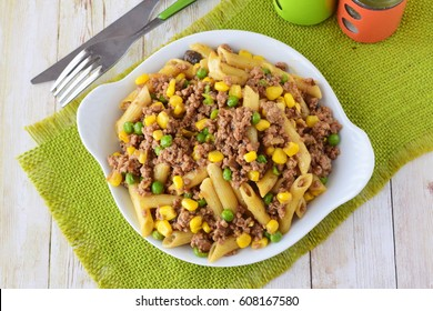 Pasta with minced meat, green peas and yellow corn in a white plate. Home cooking. Healthy eating concept