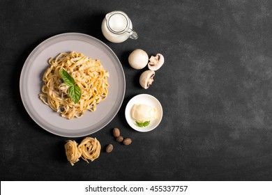 Pasta with mushrooms and bechamel sauce. Ingredients for spaghetti on a black background.  Copy space for your text