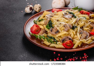 Pasta with mushrooms, cheese, spinach, rukkola and cherry tomatoes. Italian dish, Mediterranean culture