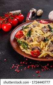 Pasta with mushrooms, cheese, spinach, rukkola and cherry tomatoes. Italian dish, Mediterranean culture