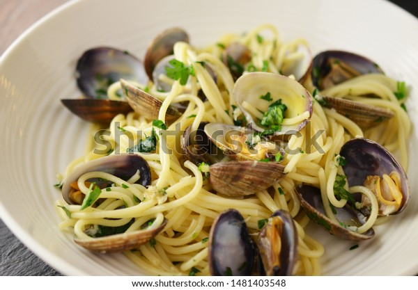 Pasta with mussels and basil on wooden table.