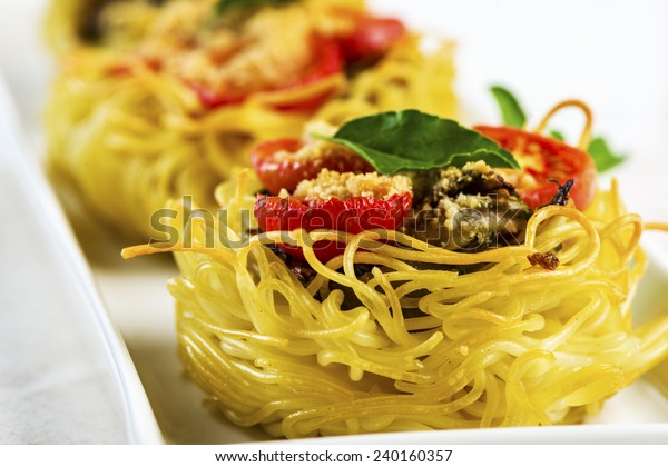 pasta nest arranged on a white porcelain plate with tomatoes parmesan and some leaves of basil