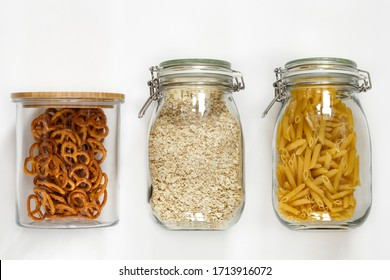Pasta, oatmeal and pretzels in glass jars on white background on kitchen.Top view.Stocks of non-perishable products on a light background.Organized home simple stylish storage no plastic, zero waste