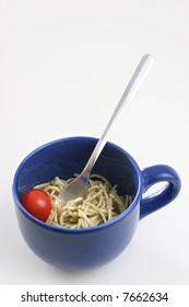 Pasta olio with a cherry tomato in a large blue ceramic cup