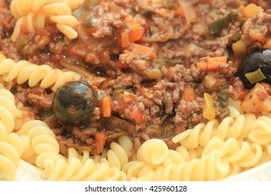 Pasta on a plate: Fusilli with ragu, cheese and black olives