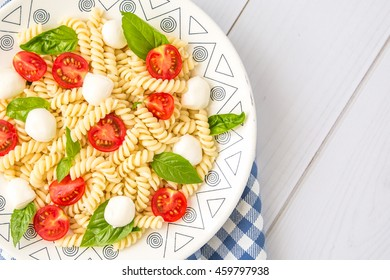 Pasta on a white ceramic plate with cherry tomatoes, mini mozzarella cheese and fresh basil on a wooden table. Italian food