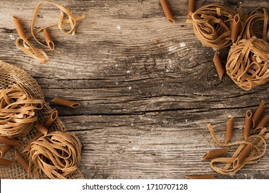 pasta on a wooden table - homemade pasta lying on a wooden, rustic table.