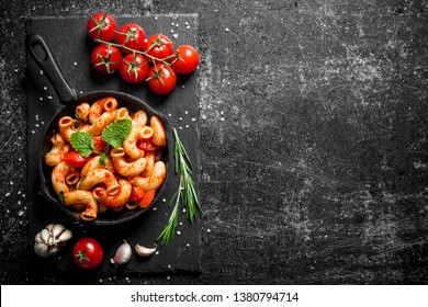 Pasta in pan with tomatoes, garlic and rosemary. On black rustic background