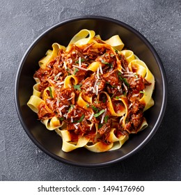 Pasta pappardelle with beef ragout sauce in black bowl. Grey background. Close up. Top view.