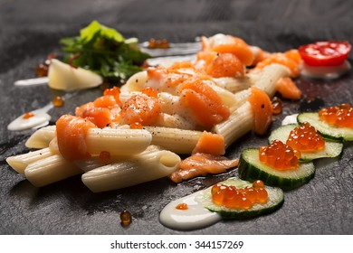 Pasta penne with salmon, caviar and fresh onion