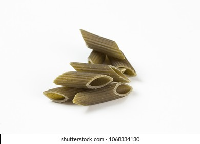 pasta penne - several raw uncooked italien green spinach noodles pasta on a heap on a white background