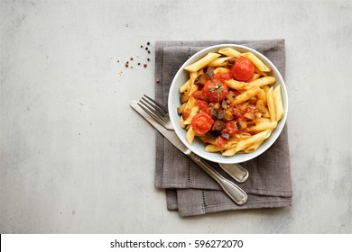 Pasta penne with tomato sauce, garlic and eggplant. Top view, empty space.