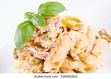 Pasta - penne with white cream sauce with bacon and jalapeño peppers on a plate, decorated with fresh basil