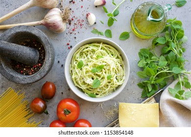 Pasta with pesto sauce and basil in a bowl. Ingredients for Italian cuisine. Top view table