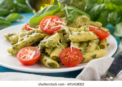 Pasta pesto with tomatoes on a blue table. Served with tomatoes, basil, olive oil, pesto, napkin, knife, fork. close-up photo